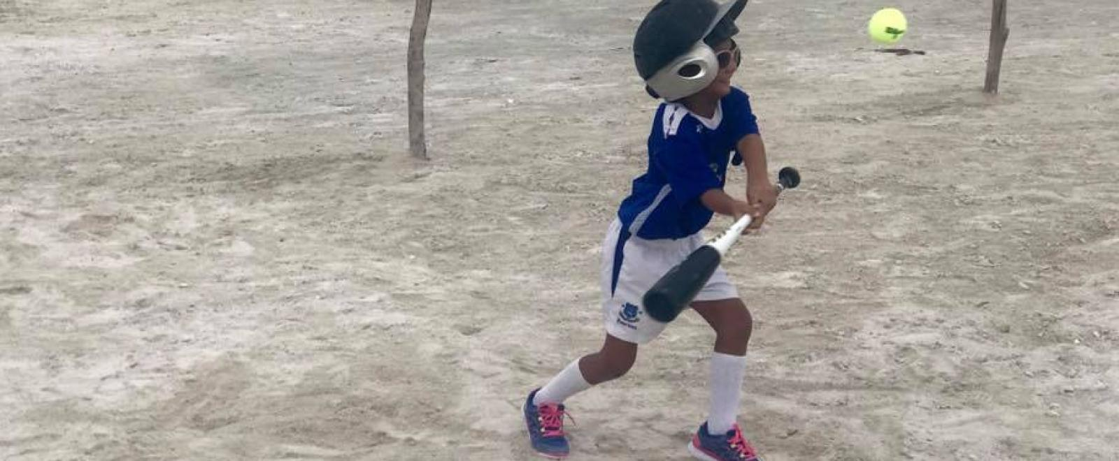 A young boy learns to play baseball during our volunteer sports coaching in schools in Belize